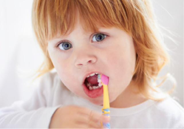 child cleans and brushes her teeth to prevent cavities in St. Helens